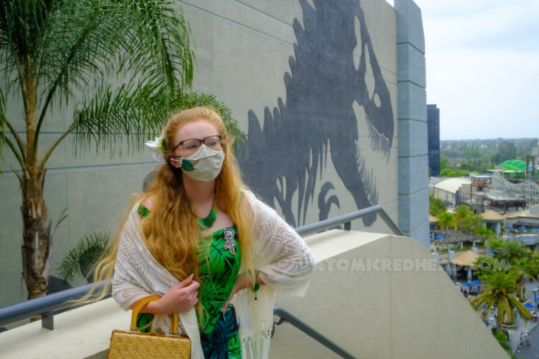 Myself standing in front of the side of the Jurassic World building, which features a massive T-Rex skeleton, wearing a dress featuring a tropical leaf and frond design, with a necklace and bracelet that also features leaves and fronds, a white shawl is wrapped around my shoulders.
