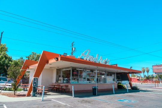 """Andre's at an angle. Two over arching """"dog legs"""" stretch across the small walk up restaurant, painted orange. A nearly all glass front has showcases the items available. A seating area is off to the left."""