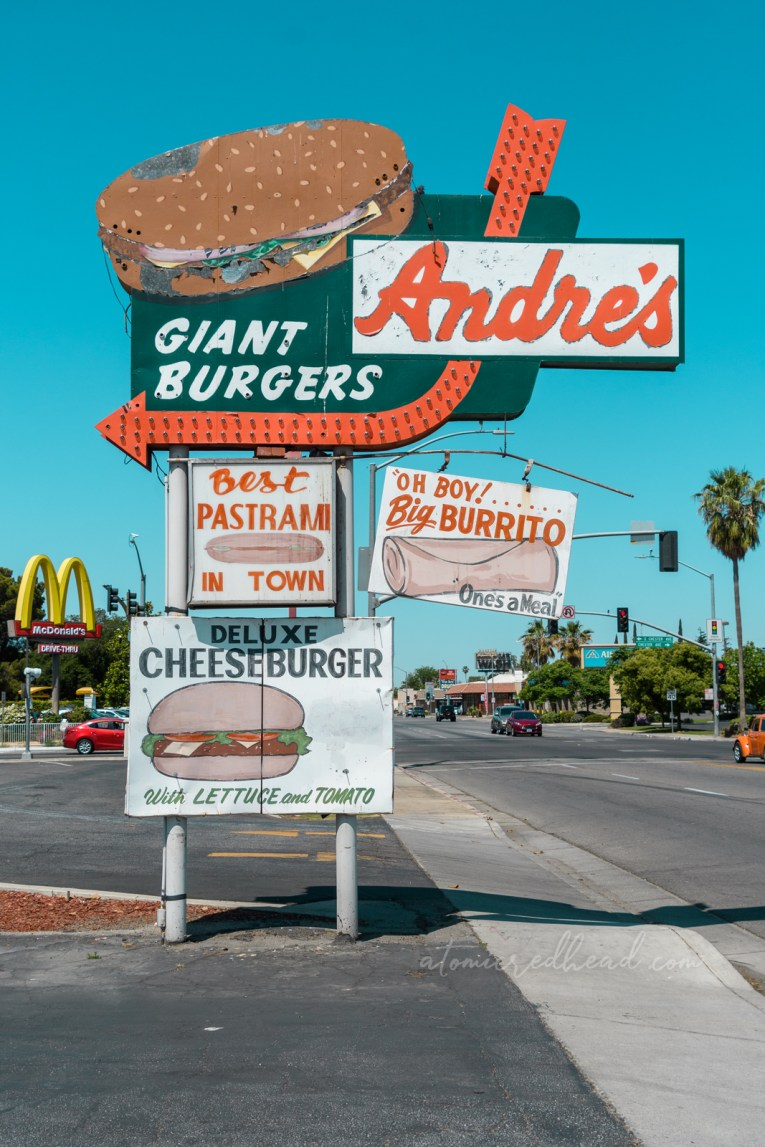 """The sign for Andre's. A large green sign reads """"Andre's Giant Burgers"""" and features a massive painted burger and an orange arrow. Other attached signs read """"Best pastrami in town"""" """"Oh Boy! Big Burrito"""" and """"Deluxe Cheeseburger with lettuce and tomato"""""""