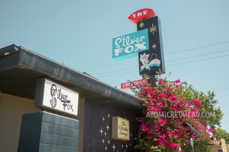 """The black building of the Silver Fox. Atop the roof sits a sign of black, red, and blue, reading """"The Silver Fox"""" featuring a neon fox. Two backlit plastic signs reside on the side of the building, one reads """"Silver Fox"""" the other reads """"Starlite Lounge"""""""