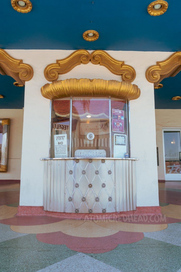 The box office, with gold trim around the top, and gold detailing below the window.