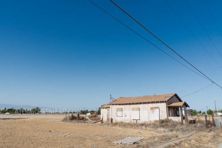 A small dilapidated tan home with boarded up windows. A sprawling dead field stretches out behind it.