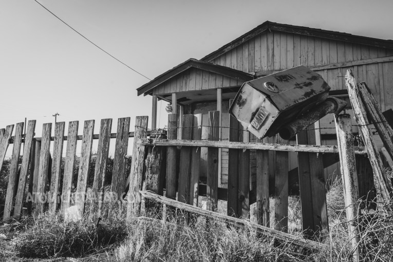 Black and white photo of an abandoned home, its mail box sits, almost about to fall off of its post.