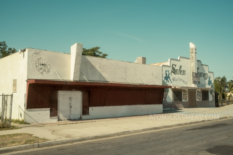 An abandoned storefront or bar, white stucco makes up the upper part, while the middle is of red painted wood.