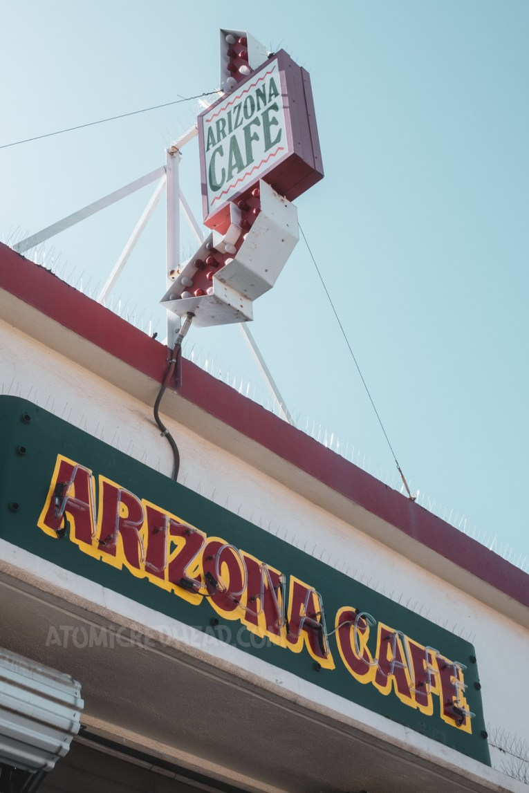 """Signage for the Arizona Cafe. An arrow with a backlit plastic sign sits on the roof, a red, yellow, and green neon sign reading """"Arizona Cafe"""" faces the front of the cafe."""