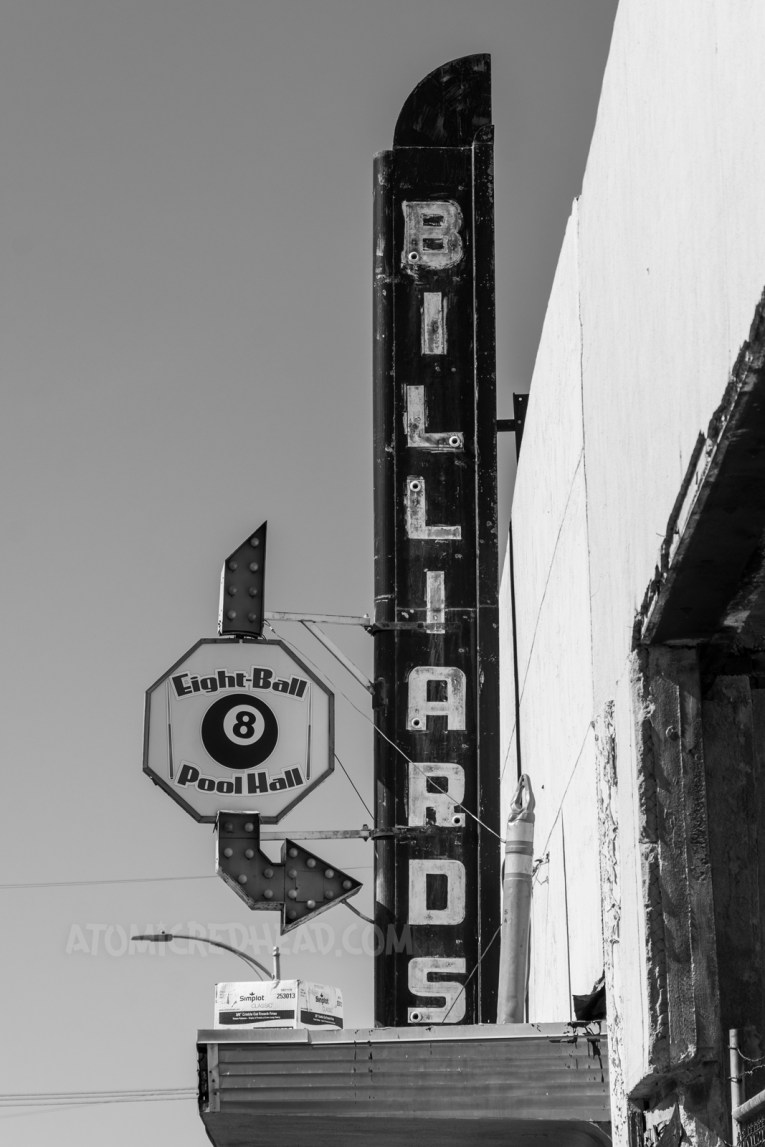 """Blade style sign for a billiard hall, reading """"Billiards"""" down in neon, an arrow next to it has a backlit plastic sign reading """"Eight Ball Pool Hall"""" and features an eight ball."""