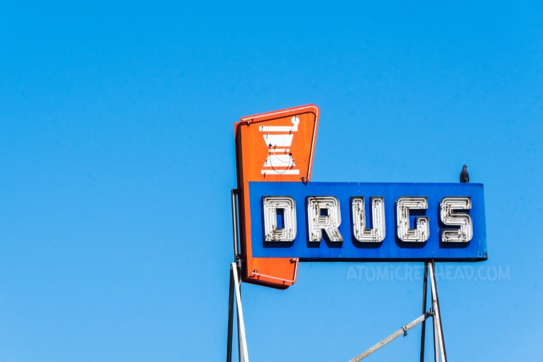 """A red, white, and blue neon sign reads """"Drugs"""""""