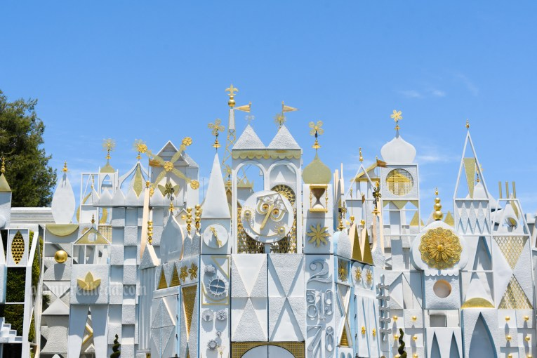 """The abstract, yet elegant facade of """"it's a small world"""" with icons from around the world in white and gold."""