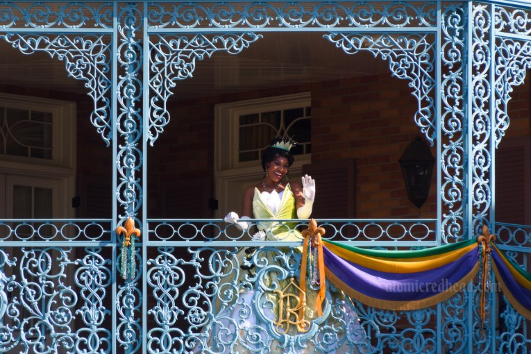 Princess Tiana waves from a balcony of curling wrought iron in New Orleans Square.