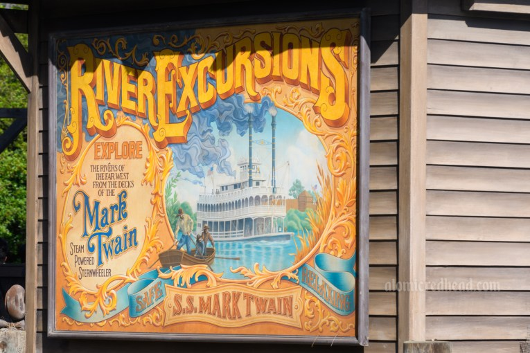 """A mural on the side of a small building features the elegant Mark Twain along the rivers. Various script reads """"River Excursions Explore the rivers of the far west from the decks of the Mark Twain steam powered sternwheeler. Safe Relaxing SS Mark Twain"""""""