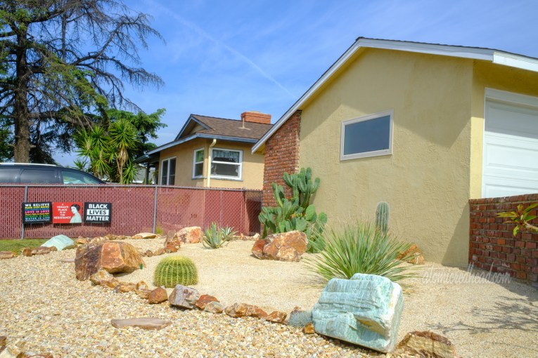 A rock pathway weaves toward the house, edged with large rocks. Cacti sit between the path and the house.