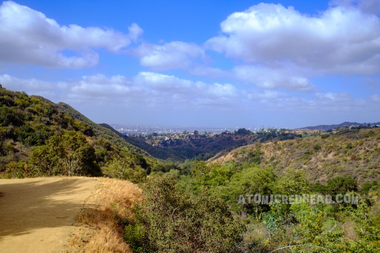 Green rolling hills give way to the Los Angeles landscape in the background.