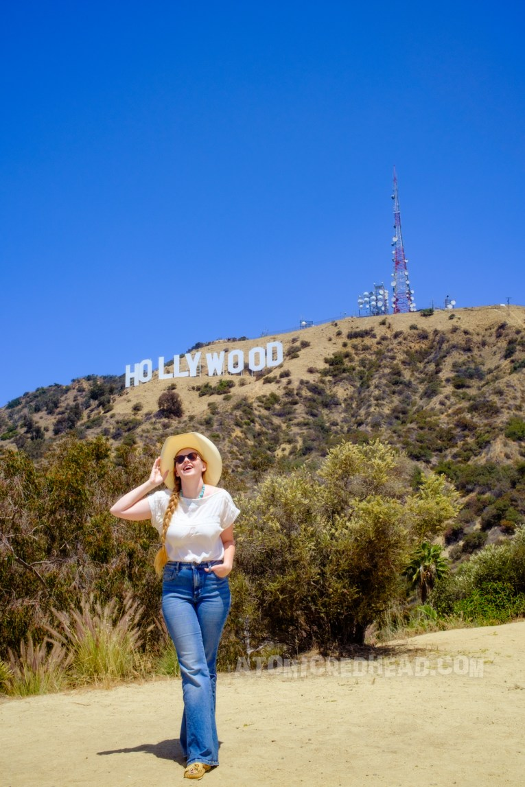 Standing in front of the Hollywood sign, wearing a cowboy hat, white peasant blouse and blue jeans.