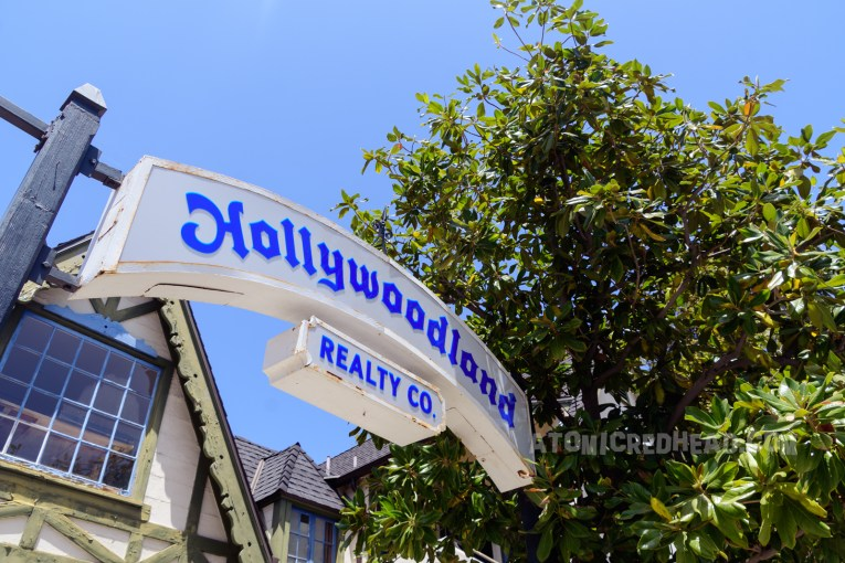 """A white arched sign reads """"Hollywoodland Realty Co."""" in gothic blue letters."""