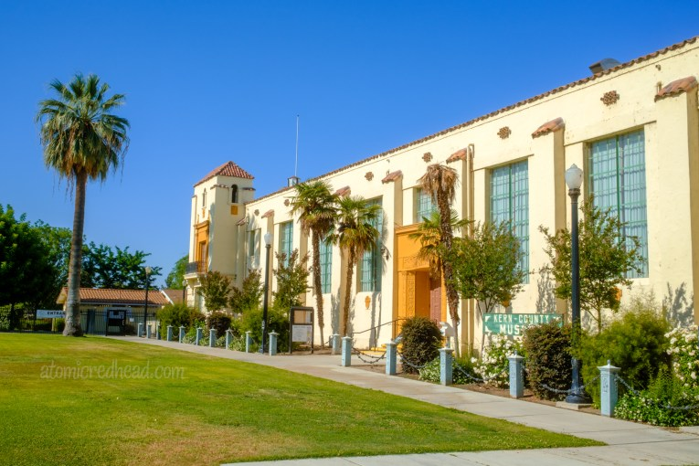 Exterior of the Kern County Museum, a long Spanish Colonial revival style building with red tile roof, and palm trees out front.