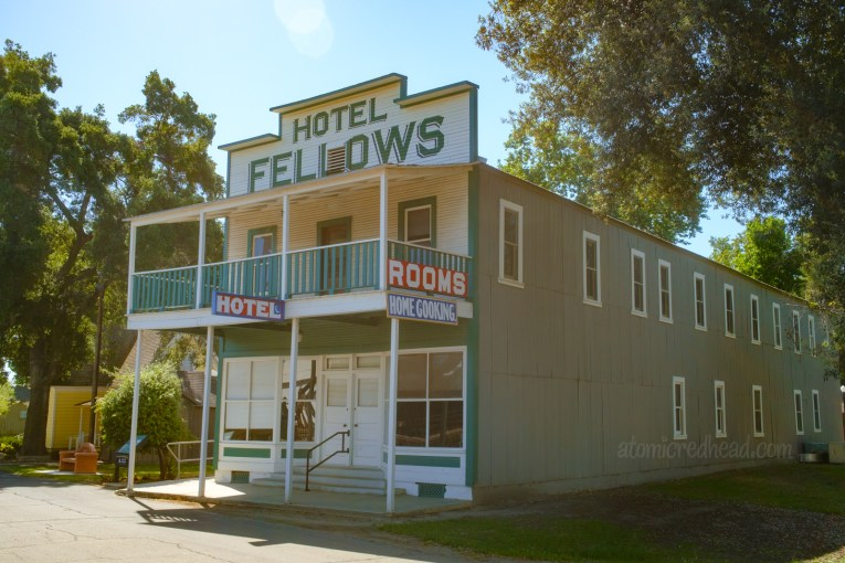 """An old west style two story hotel, with balcony. Painted grey, with a white front, and blue trim. Along the top in large blue letters reads """"Hotel Fellows"""" signs hanging from the balcony read """"Rooms Home Cooking"""""""