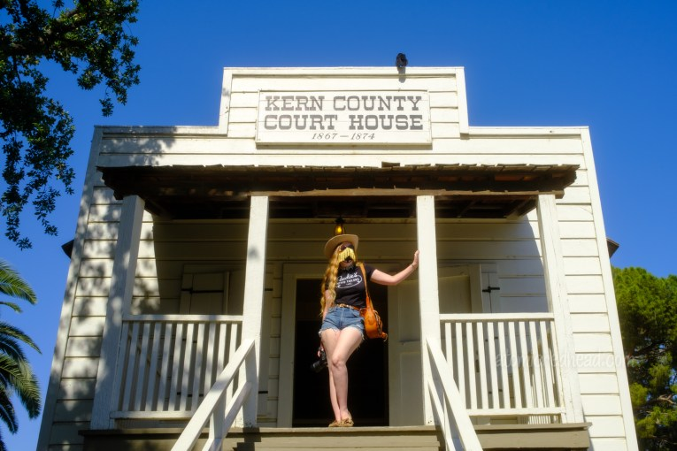 Myself standing on the porch of the old Kern County Court House, a white, old west style building.