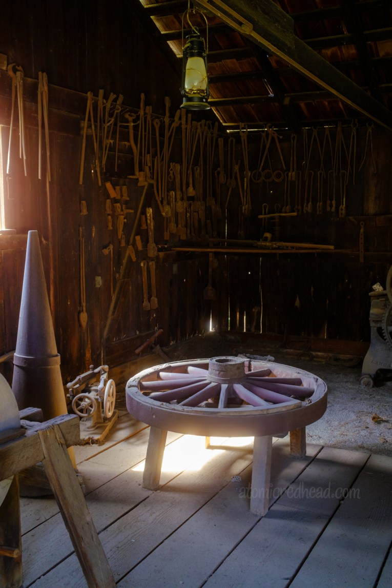Inside of the blacksmith shop. A variety of tools line the walls, a wagon wheel sits awaiting repair.