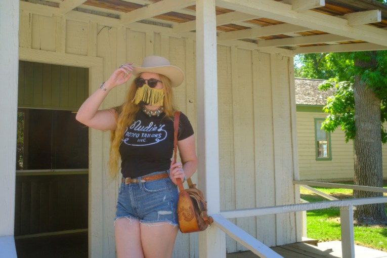 """Myself standing on the porch of the newspaper building, wearing a white cowboy hat, black shirt reading """"Nudie's Rodeo Tailor"""", jean shorts, and a tooled leather purse that resembles a saddle."""