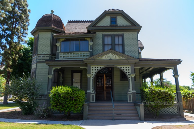 A beautiful Victorian home painted in a sage green with dark green trim.