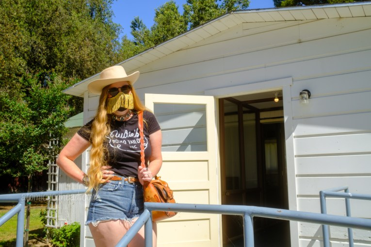 """Myself, standing in front of Haggard's home, wearing a white cowboy hat, black shirt reading """"Nudie's Rodeo Tailor"""", jean shorts, and a tooled leather purse that resembles a saddle."""