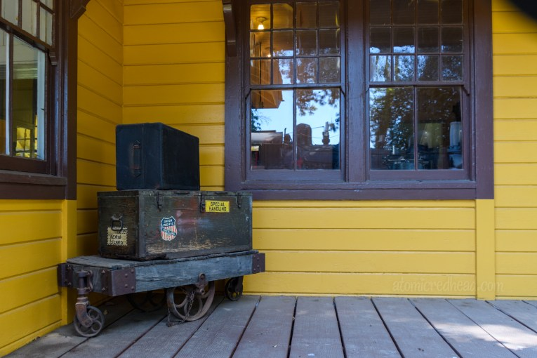 Old trucks sit on the platform of an old railroad station, which is painted a sunflower yellow with brown trim.