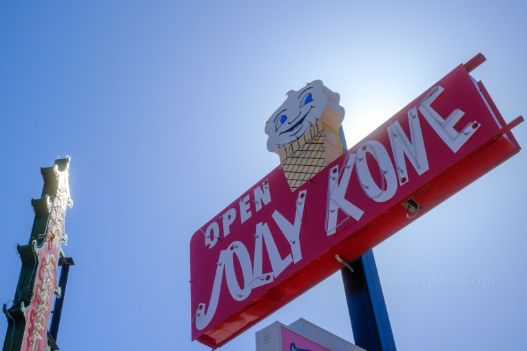 """A red neon sign with white letters reading """"Open Jolly Kone"""" and a small ice cream cone on top, with a face on the ice cream."""