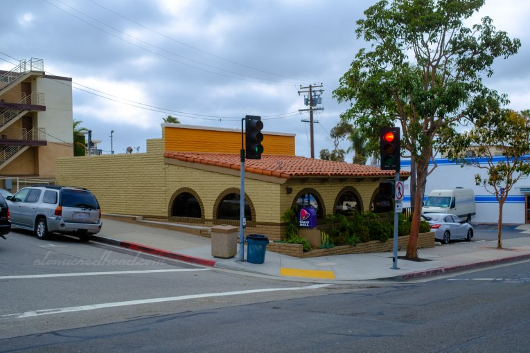 Three-quarter angle of the Taco Bell, showcasing the seam where the dining room was added to the original front.