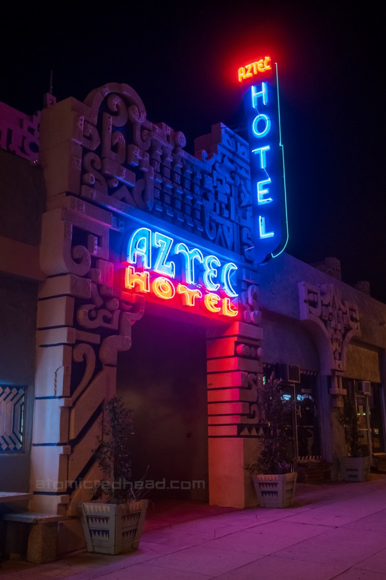 """Exterior of the Aztec at night. A blue and red blade style sign juts out from the front, and a red and blue sign is lit above the doorway, each read """"Aztec Hotel."""""""