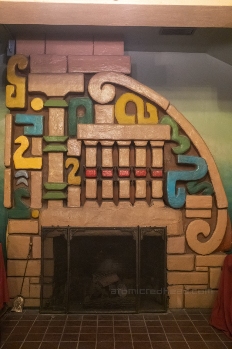 Fireplace in the lobby, which features an intricate painted Mayan design above the fireplace opening.