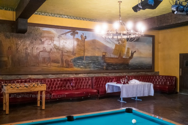 Mural of a ship arriving on shores painted on the wall of the old supper club, which today serves as a dining and game room.