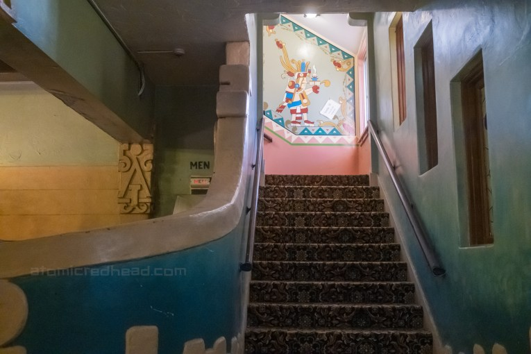 Staircase leading up to the rooms, the landing wall features a mural of an ancient god.