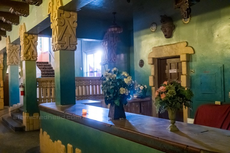 The check in counter in the lobby, which features pillars of Mayan inspired decor at the top.
