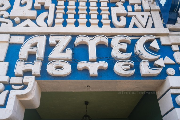 """Close-up of sculpted concrete to read """"Aztec Hotel"""" which is outlined in neon."""