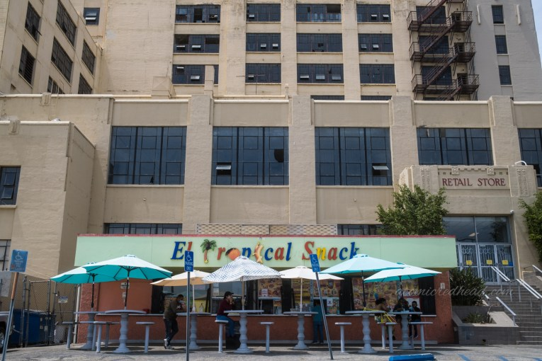 El Tropical Snack, a colorfully painted snack bar attached to the side of the massive pale yellow building.
