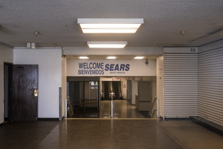 """Just inside the doors of the Sears, with a smaller staircase going down into the store. Blue letters spell out """"Welcome Sears Boyle Heights"""""""