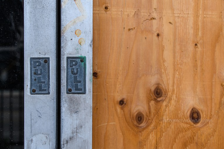 """Close-up of the boarded up front doors, with small plaques on the edge reading """"PULL"""""""