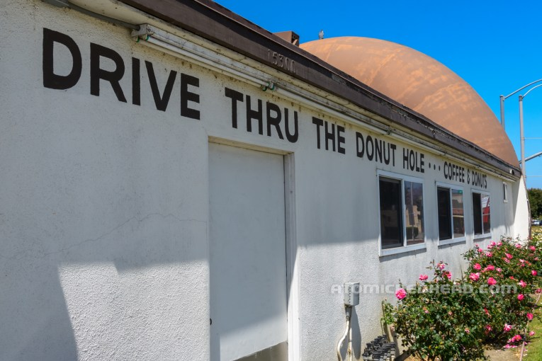 """The white kitchen that connects the two large donuts, with black text that reads """"Drive thru the Donut Hole...Coffee & Donuts"""""""
