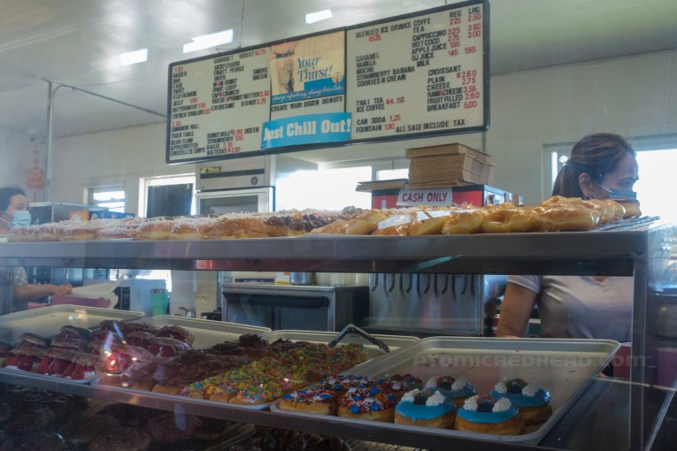 Behind a window are racks of various donuts. Above a menu board features the variety of items available.