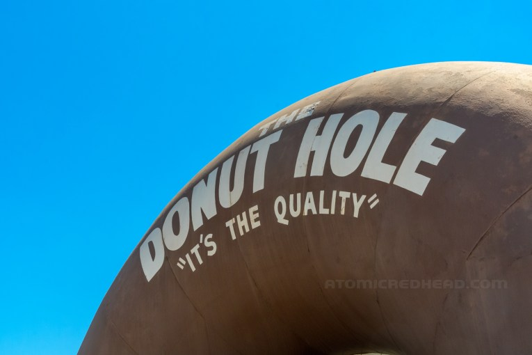 """Close-up of the text above the opening, reading """"The Donut Hole 'It's the Quality'"""""""