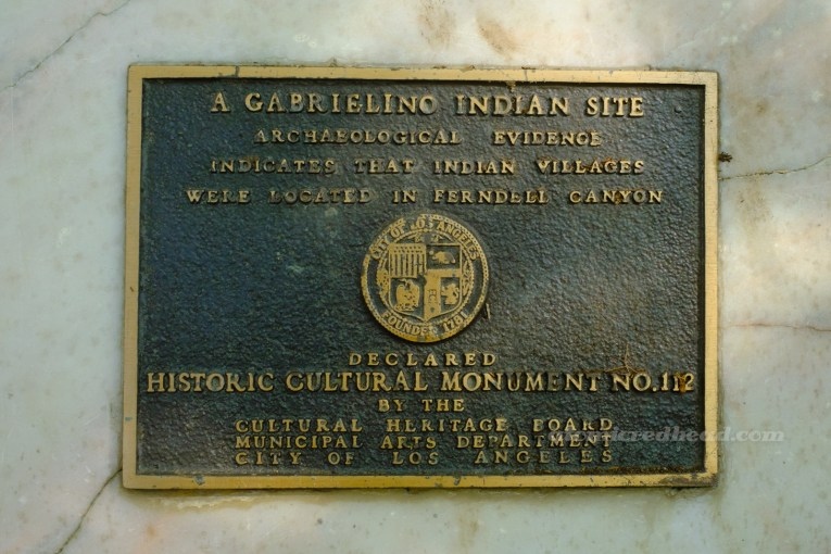 """A bronze plaque reading """"A Gabrielino Indian Site. Archaeological Evidence indicates that Indian Vilages were located in Ferndell Canyon. Declared Historic-Cultural Monument No. 112 by the Cultural Heritage Board Municipal Arts Department City of Los Angeles."""""""