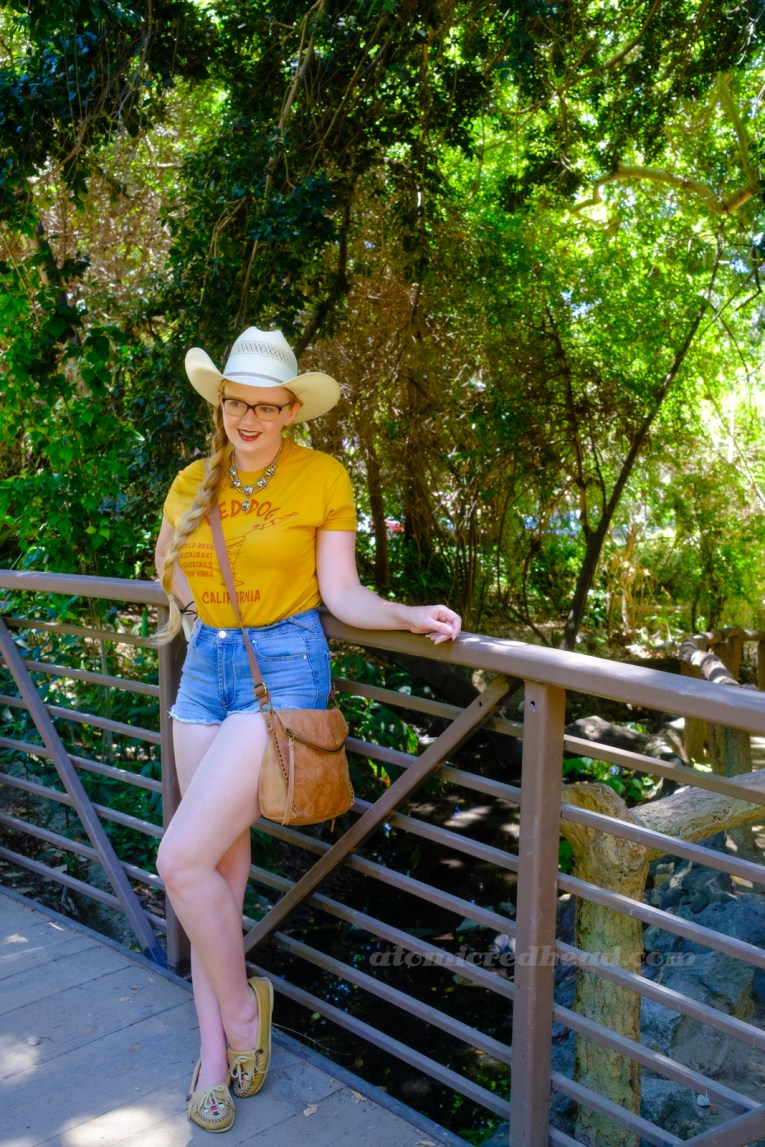 """Myself, wearing a cream straw cowboy hat, yellow shirt red text reading """"Red Dog California Cold Beer Restaurant Cocktails Good Vibes"""" and featuring a woman diving into a martini glass, and jean shorts, standing in front of a rock grotto."""