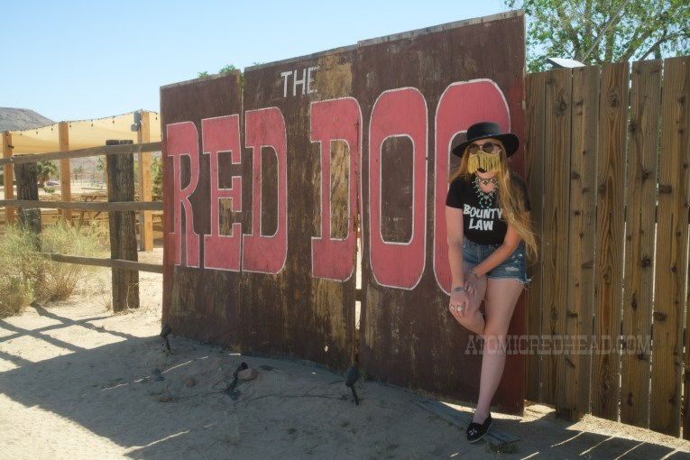 """Myself, wearing a black cowboy hat, black tee reading """"Bounty Law"""" and jean shorts, leaning against a large sign reading """"The Red Dog"""" in large red letters."""
