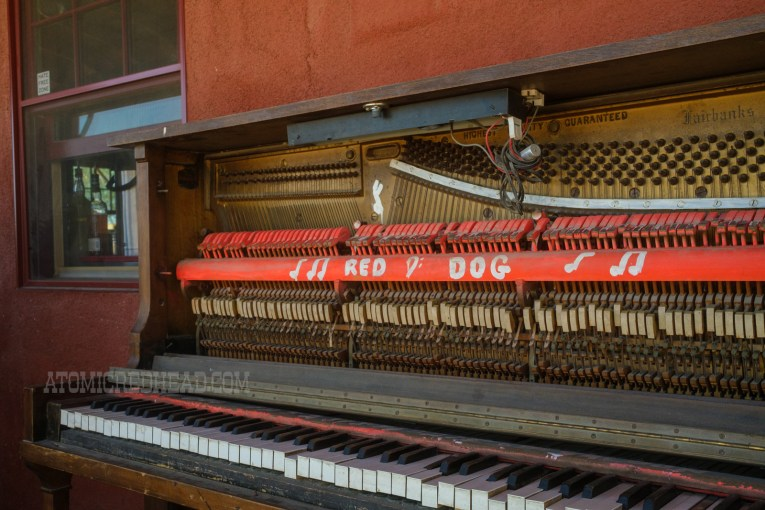 """An old piano sits on the porch, painted on it reads """"Red Dog"""""""