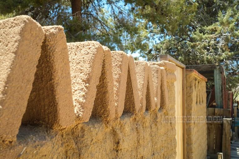 Adobe bricks make up a small wall, at the top the bricks form a zig-zag pattern.