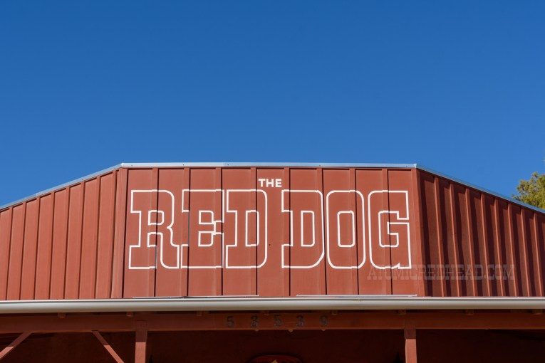 """Close-up of above the entrance, which reads """"The Red Dog"""" in red letters outlined in white."""