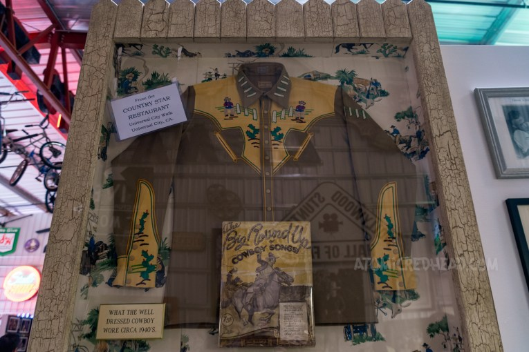 """A framed western wear shirt, featuring a yellow yoke and light brown body. Embroidered on the yoke is a cowboy by a fence. In the upper left is a small piece of paper that reads """"From the Country Star Restaurant, Universal City Walk, Universal City, CA."""""""