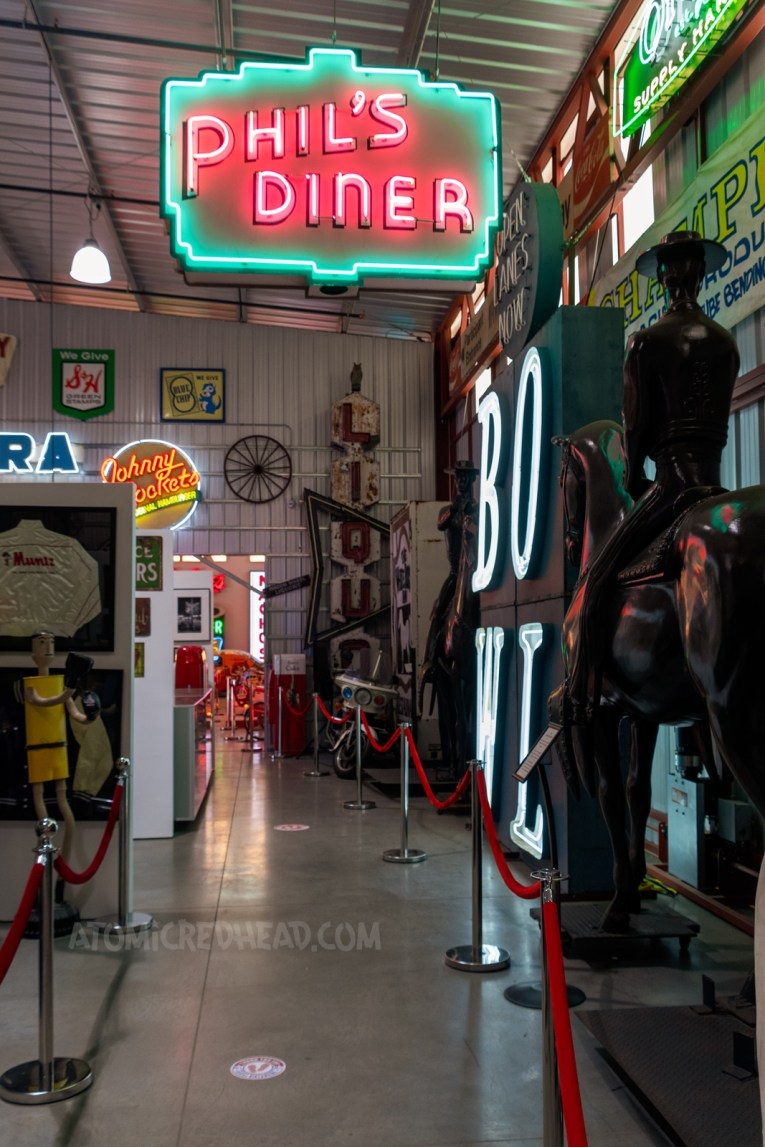 """One of the rooms of Valley Relics, filled with all sorts of odds and ends, two larger than life statues of cowboys on horses, neon sign reading """"Johnny Rocket's"""" another reading """"Phil's Diner"""" framed clothing, various metal signs."""