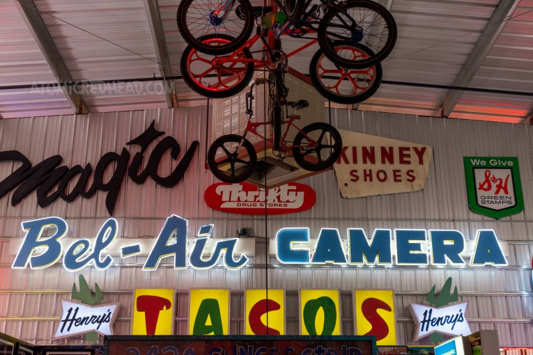 """BMX style bikes hang from the ceiling. A variety of signs hang on the wall, one reads """"Bel-Air Camera"""" another reads """"Tacos"""" and another reads """"Magic"""""""