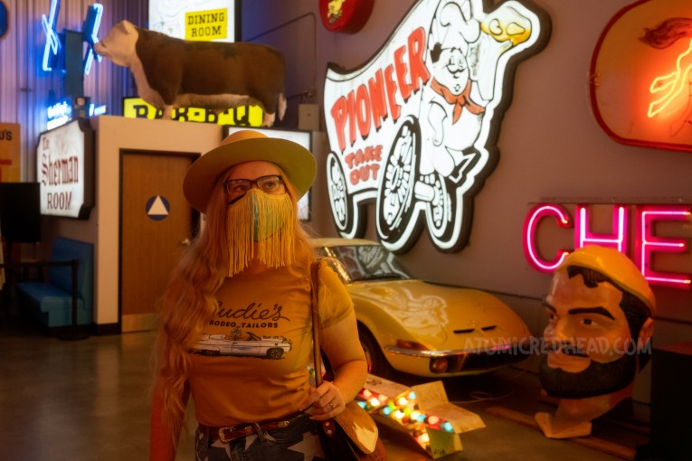 """Myself, wearing a cream cowboy hat, yellow shirt with a large white Cadillac and script reading """"Nudie's Rodeo Tailor"""" standing in front of a large sign for Pioneer Chicken, which features a chef sitting on a covered wagon."""